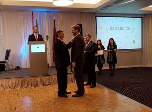 Посол Казахстана вручает медаль Андрею Клементьеву